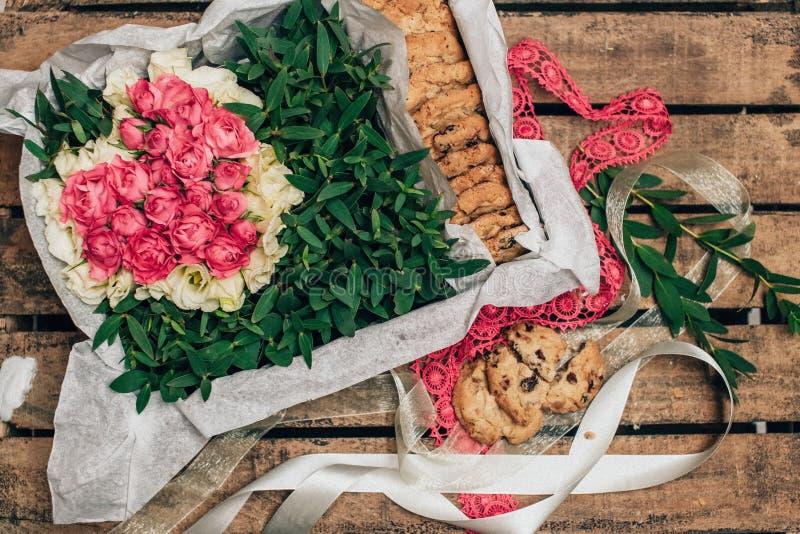 Encajone con las rosas y las galletas de las flores en una tabla de madera en un paquete hermoso imagenes de archivo
