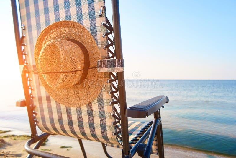 Encalhe acessórios, chapéu do ` s da mulher afixado à parte traseira da cadeira de plataforma fotos de stock royalty free