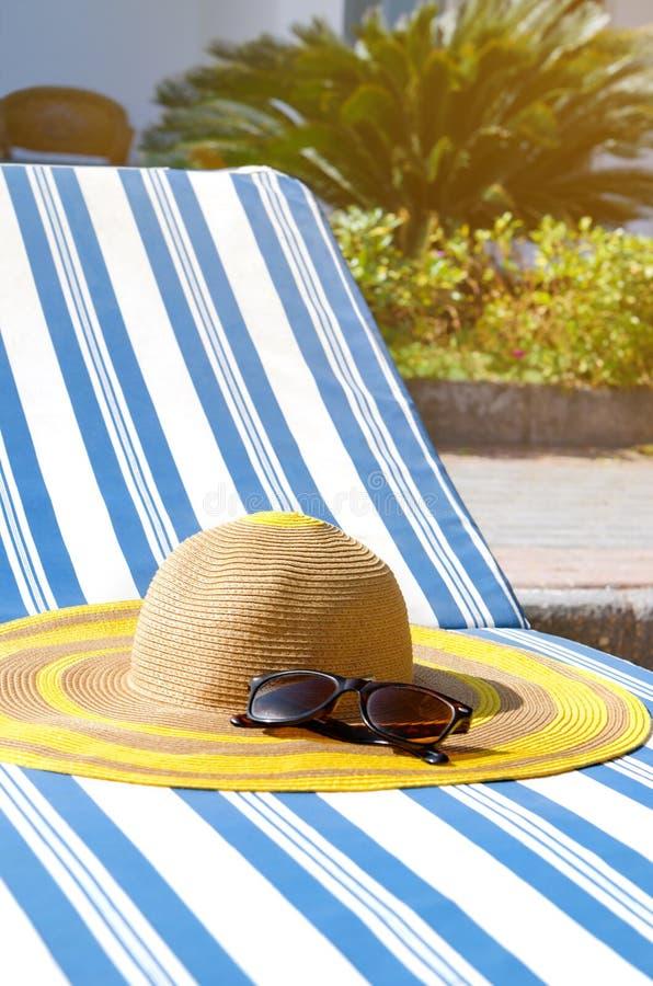 Encalhe acessórios na cadeira de plataforma pela associação Conceito das férias de verão fotografia de stock