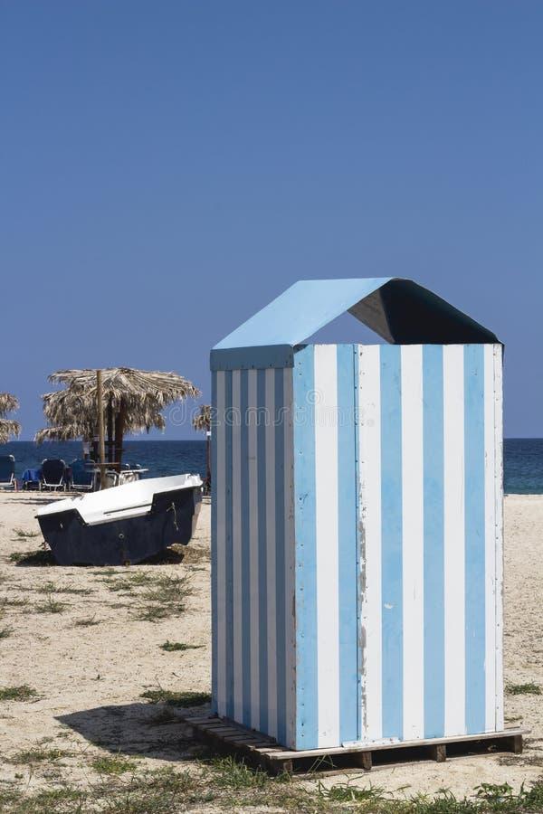 Encalhe a cabine com tiras azuis e do branco na areia em Grécia retro foto de stock