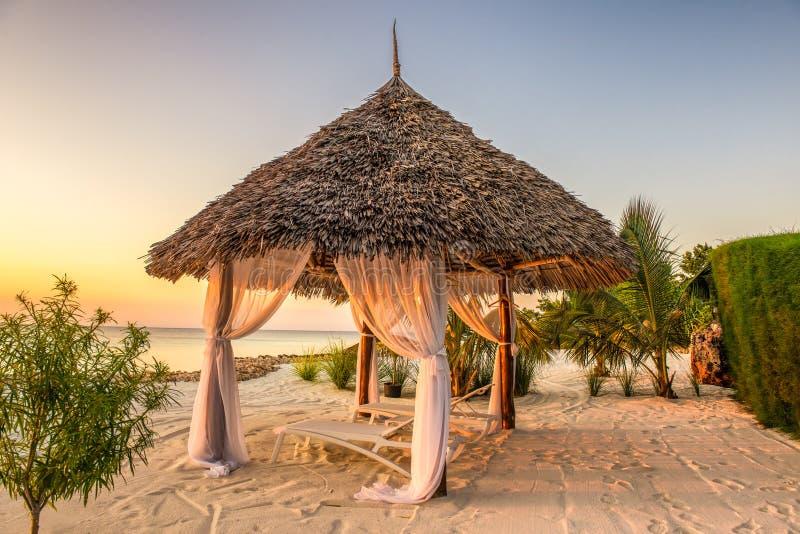 Encalhe cadeiras de sala de estar no por do sol, Zanzibar, Tanzânia imagens de stock