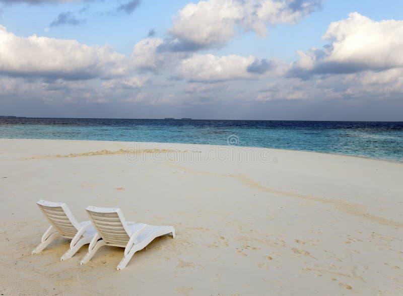 Encalhe cadeiras de sala de estar em uma praia tropical bonita da areia com o céu azul nebuloso maldives fotografia de stock