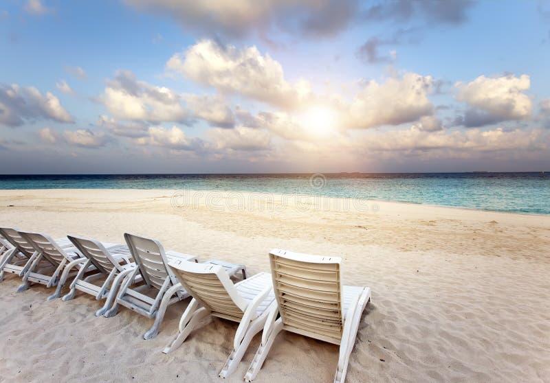 Encalhe cadeiras de sala de estar em uma praia tropical bonita da areia com o céu azul nebuloso maldives imagem de stock