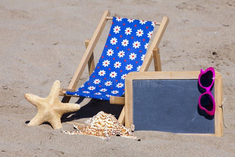 Encalhe a cena com cadeira, óculos de sol e quadro-negro de Sun foto de stock