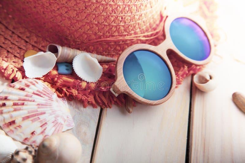 Encalhe cockleshells do chapéu dos vidros dos acessórios na plataforma de madeira imagens de stock