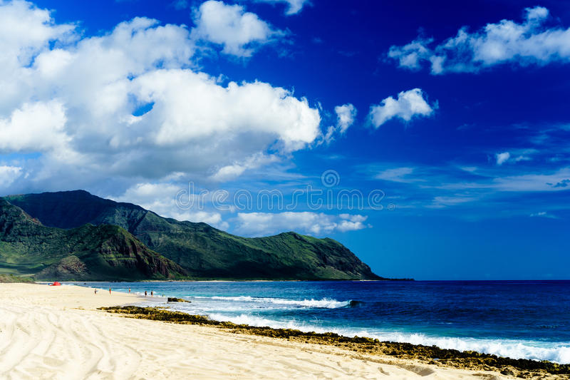 Encalhe com as ondas brancas da areia e do azul entre montanhas luxúrias fotos de stock