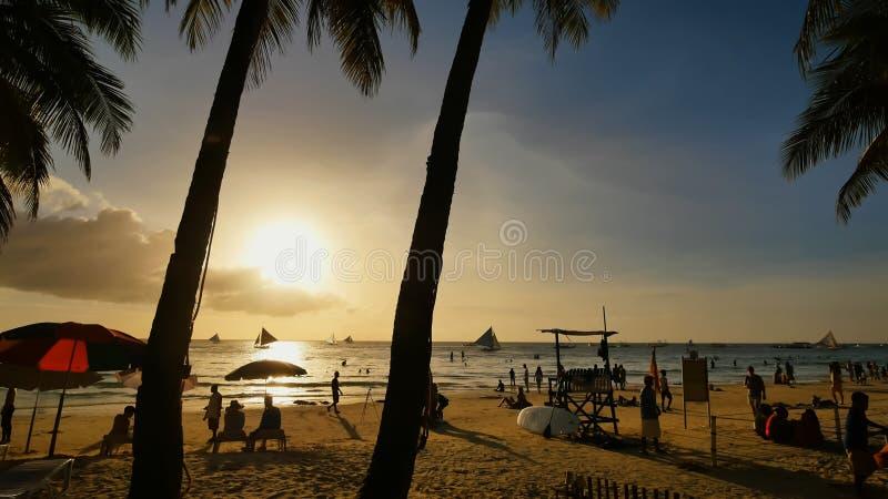 Encalhe com as silhuetas dos turistas entre palmeiras na ilha de Boracay Palmeiras nos raios do por do sol fotografia de stock royalty free