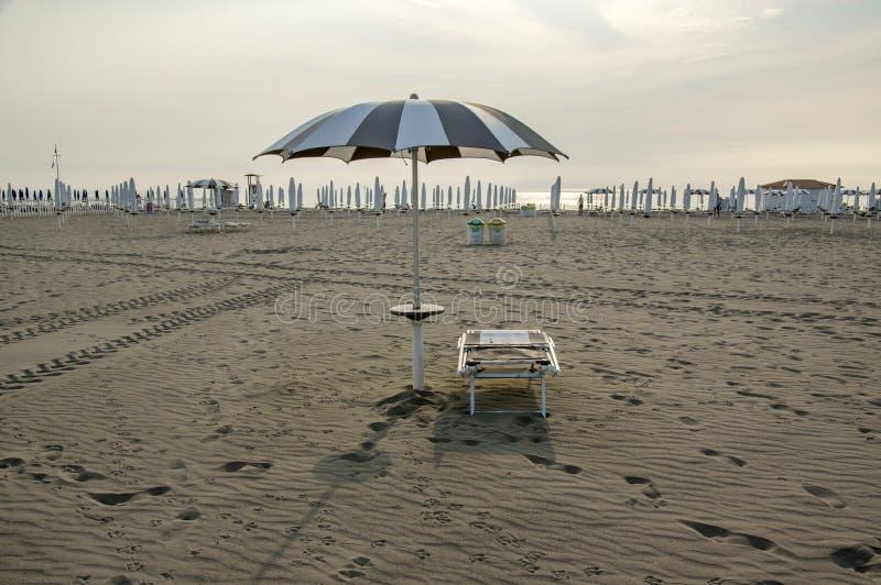 Encalhe com guarda-chuvas fechados, apronte um vadio do sol e o guarda-chuva aberto, cena romântica, amanhecer em Sottomarina, It fotos de stock royalty free