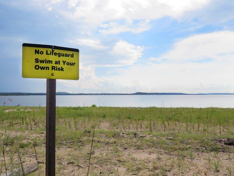 Encalhe, nenhuma salva-vidas, nade a seu próprio risco o signage fotografia de stock