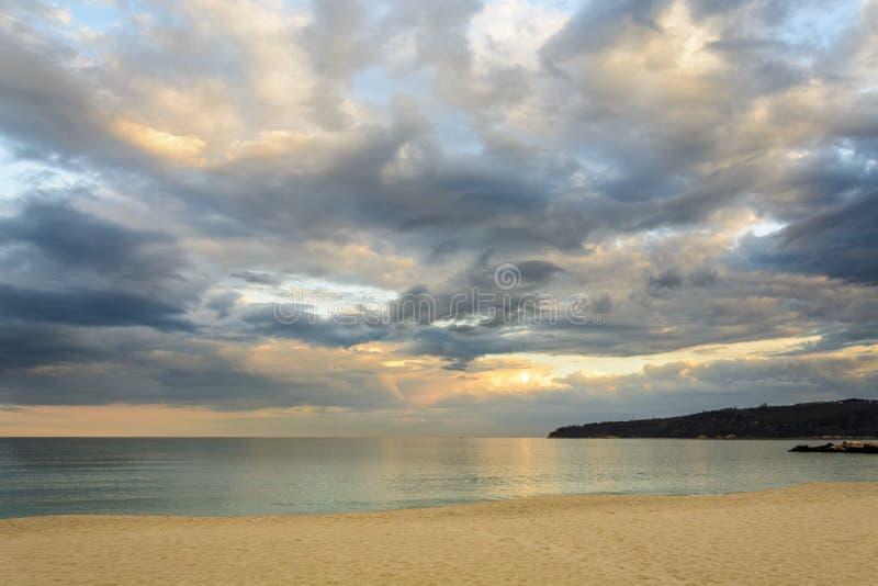 Encalhe no por do sol, nuvens dramáticas sobre o mar imagens de stock