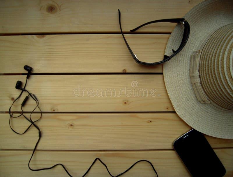 Encalhe o chapéu, os óculos de sol, o telefone celular e os fones de ouvido em um fundo de madeira, horas de verão, férias imagem de stock