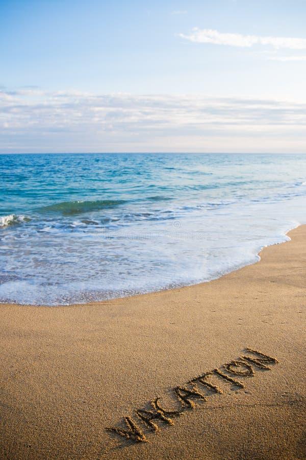 Encalhe o fundo com as férias da palavra escritas na areia fotografia de stock royalty free