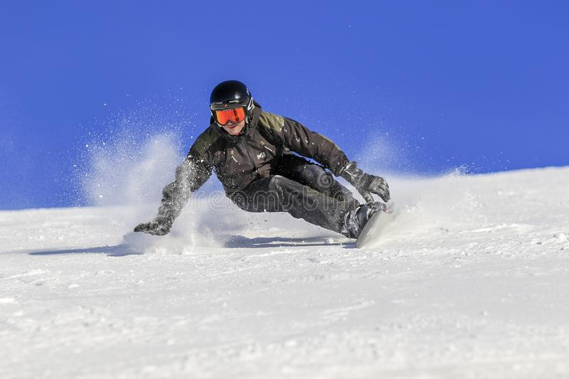 Snowboarder level pro touch the snow. ENCAMP - ANDORRA - DECEMBER - 12 - 2016 snowboarder level pro going fast on the ski slope on a sunny and snowy day, he stock photography