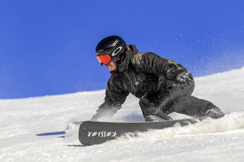 Snowboarder level pro, extreme ryder man. ENCAMP - ANDORRA - DECEMBER - 12 - 2016 snowboarder level pro going fast on the ski slope on a sunny and snowy day, he royalty free stock images