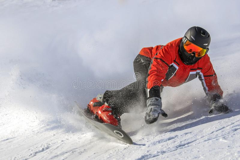 Snowboarder level pro and a lot of snow. ENCAMP - ANDORRA - JANUARY - 25 - 2017 snowboarder level pro dressed in red throws snow in an extreme move, on a sunny royalty free stock photography