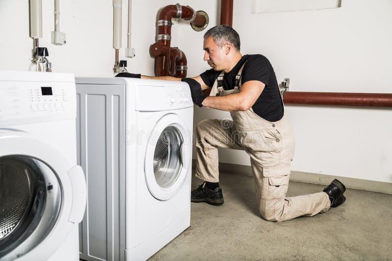 Encanador em reparos uniformes dentro da máquina de lavar na lavanderia imagens de stock royalty free