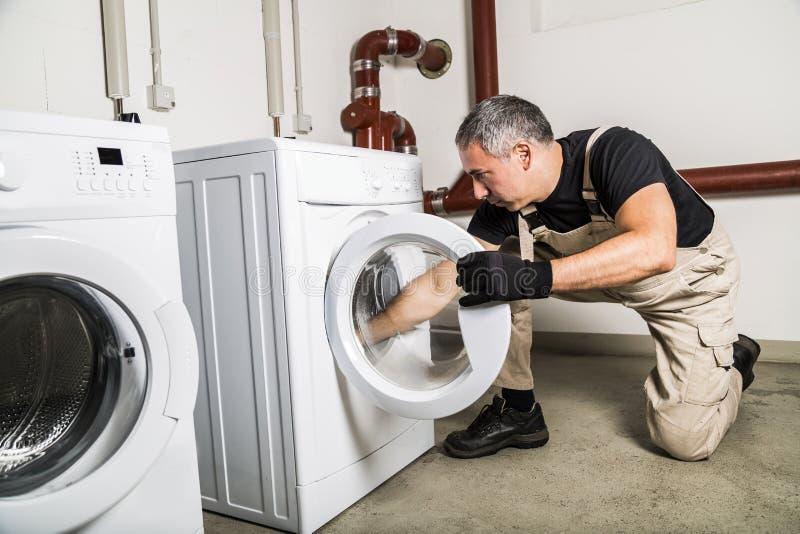Encanador em reparos uniformes dentro da máquina de lavar na lavanderia foto de stock royalty free
