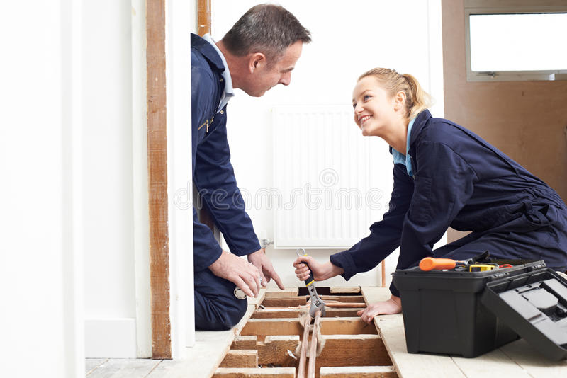 Encanador And Female Apprentice que cabe o sistema de aquecimento central fotografia de stock royalty free