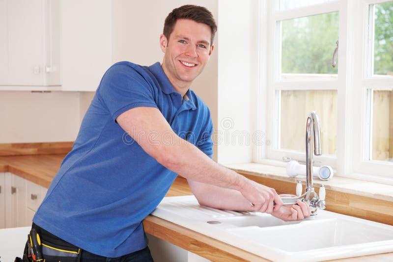 Encanador Fixing Kitchen Tap com chave ajustável imagens de stock royalty free