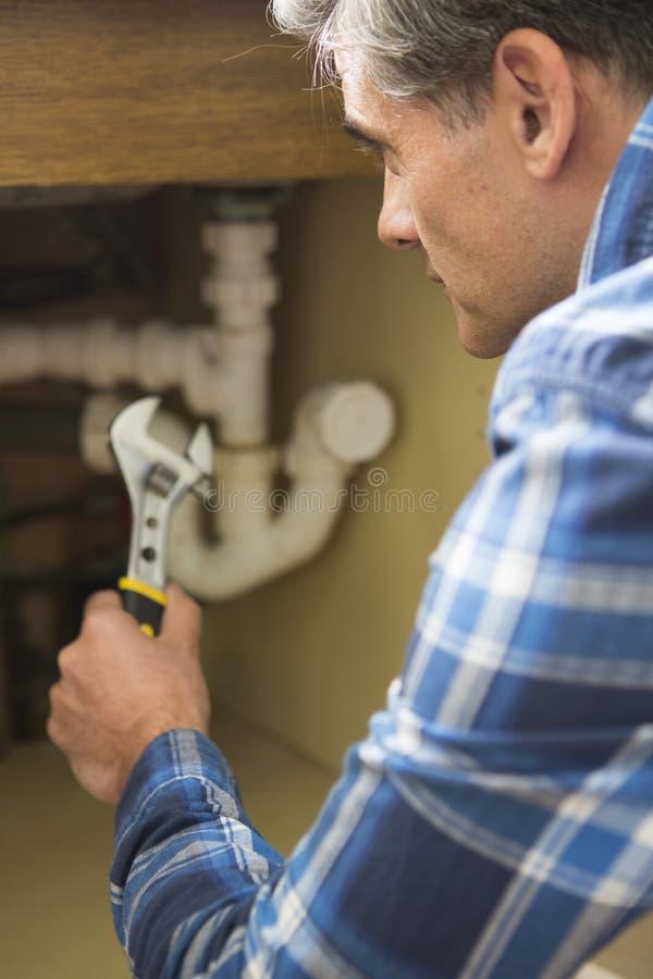 Encanador Working On Pipes sob o dissipador doméstico imagem de stock