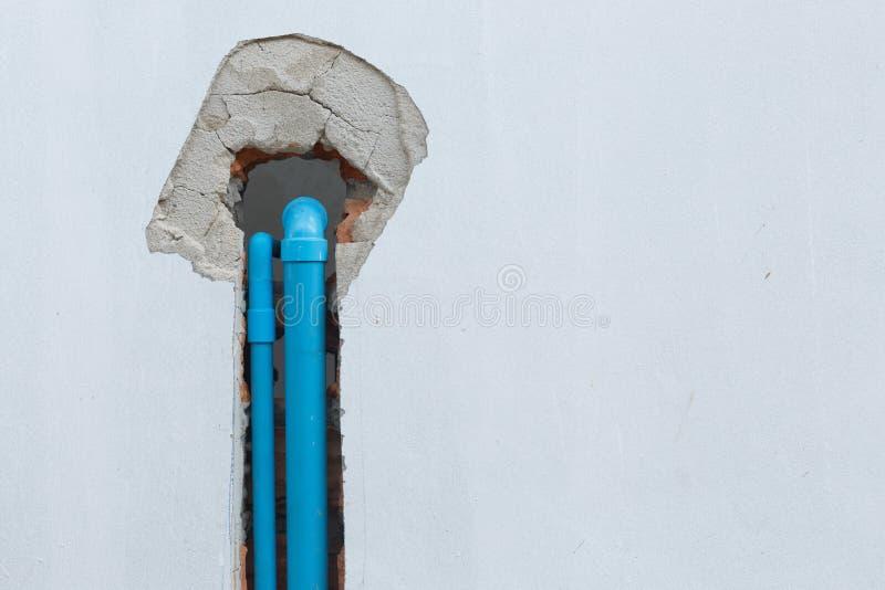 Encanamento do pvc da tubulação de água sob a parede do cimento no canteiro de obras imagens de stock
