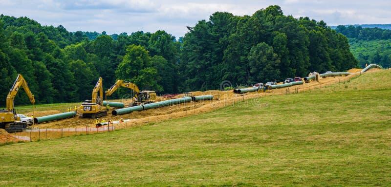 Encanamento do vale da montanha usando o equipamento de construção pesado - 2 imagens de stock