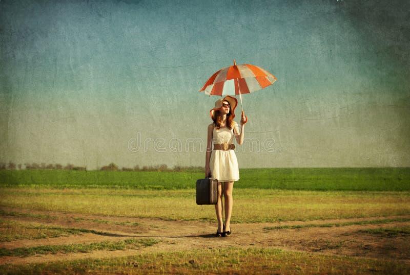 Encantadora do ruivo com guarda-chuva e mala de viagem no país da mola fotografia de stock royalty free