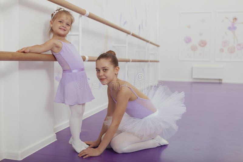 Encantando duas bailarinas novas que praticam na classe do bailado fotos de stock