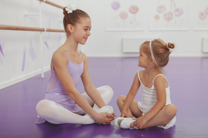 Encantando duas bailarinas novas que praticam na classe do bailado fotos de stock royalty free