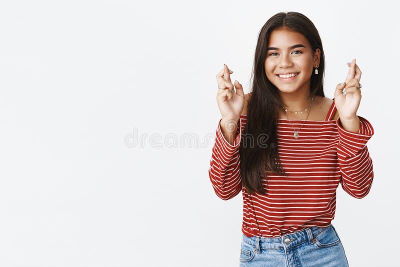 Encantando a jovem mulher esperançosa e otimista acredite o sonho para vir os dedos verdadeiros do cruzamento para a boa sorte e  imagens de stock royalty free