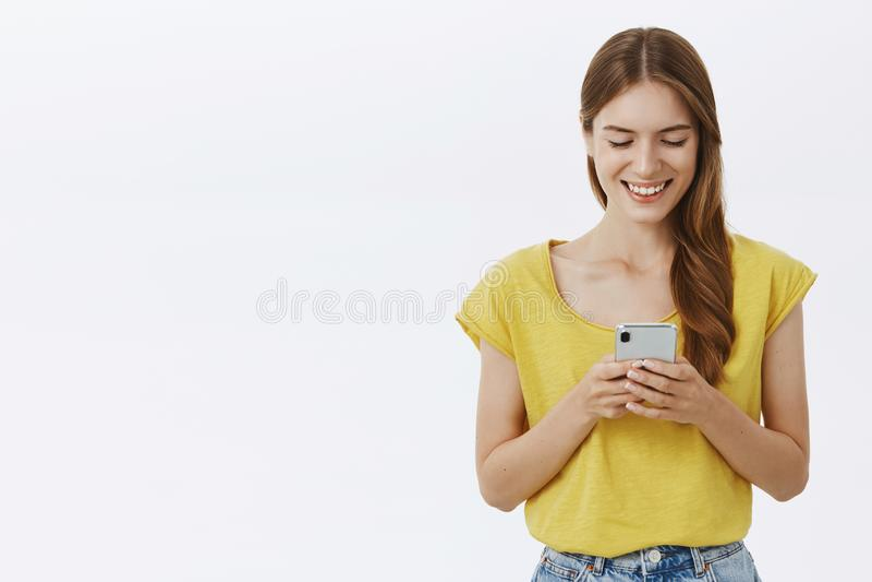 Encantando o estudante fêmea novo comunicativo e carismático no t-shirt amarelo com sorriso bonito do smartphone da terra arrenda foto de stock royalty free