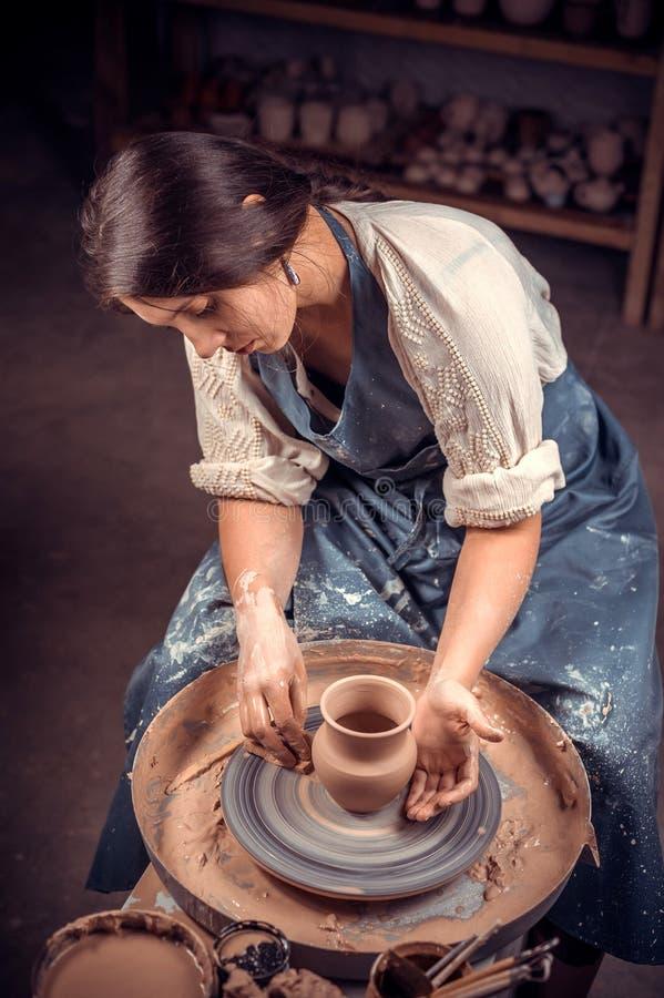 Encantando trabalhos novos e alegres da mulher com argila em uma roda de oleiro handicraft imagens de stock