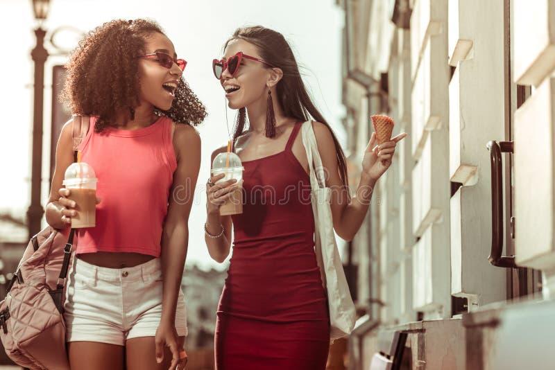 Encantar de cabelo escuro bronzeado surpreendeu as mulheres chocadas que andam as ruas foto de stock