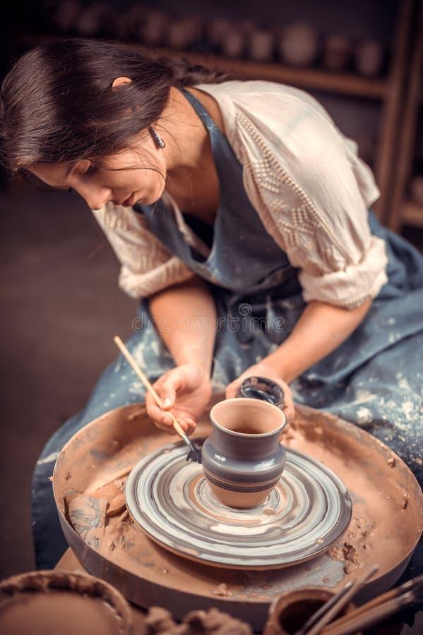 Encantar a mulher nova e alegre demonstra o processo de fazer pratos cerâmicos usando a tecnologia velha handmade imagens de stock