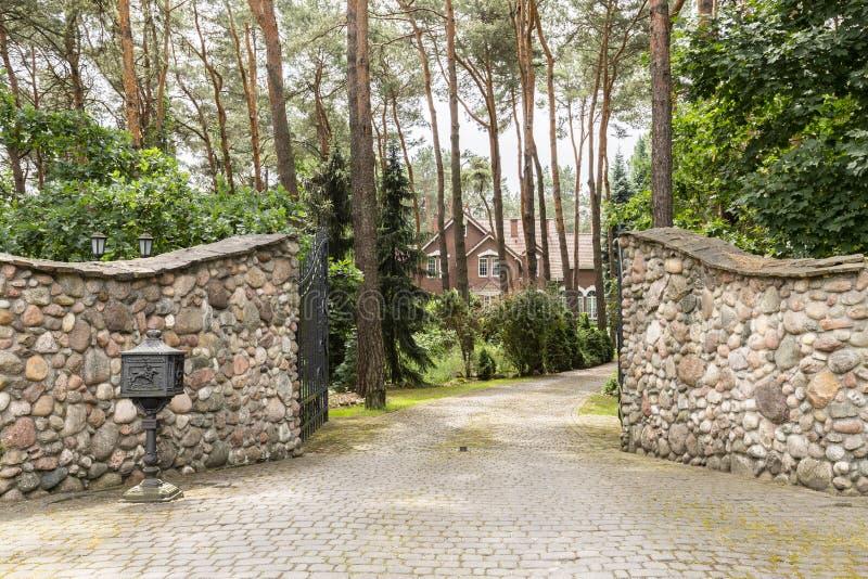 Encante la puerta a una casa rústica, inglesa en el bosque con el ston fotografía de archivo