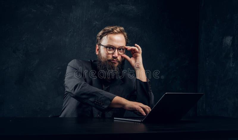 Encargado barbudo que trabaja detrás de un ordenador portátil imagen de archivo