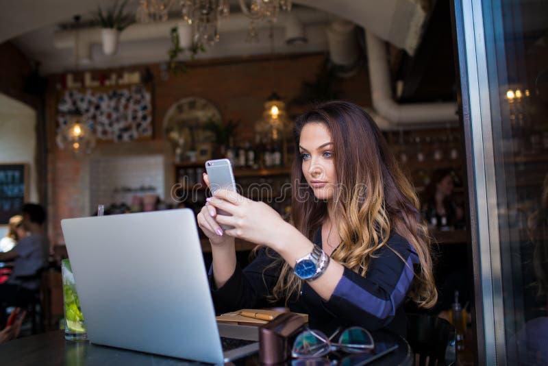 Encargado contento de sexo femenino bonito usando los apps imagen de archivo