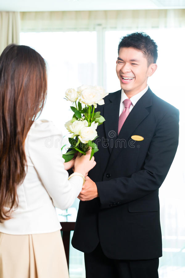 Encargado de hotel chino asiático que acoge con satisfacción a la huésped del VIP fotografía de archivo libre de regalías
