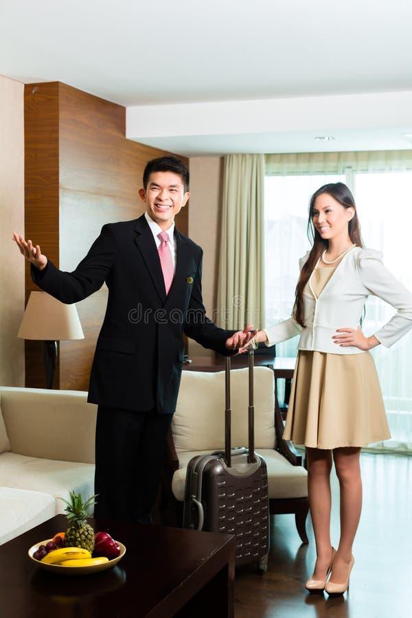 Encargado de hotel chino asiático que presenta la habitación fotos de archivo