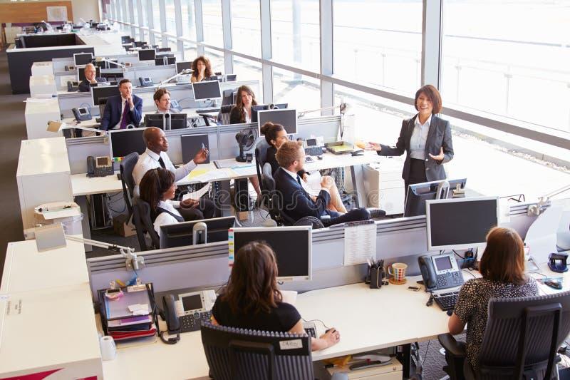 Encargado de sexo femenino asiático que se dirige a trabajadores en oficina abierta del plan fotografía de archivo