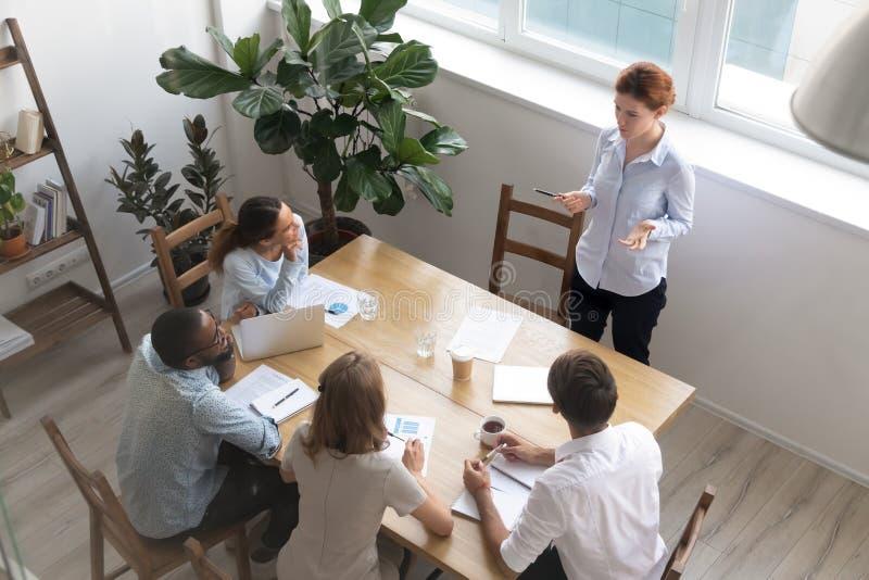 Encargado de sexo femenino del líder que habla con la reunión principal de los empleados, visión superior imágenes de archivo libres de regalías