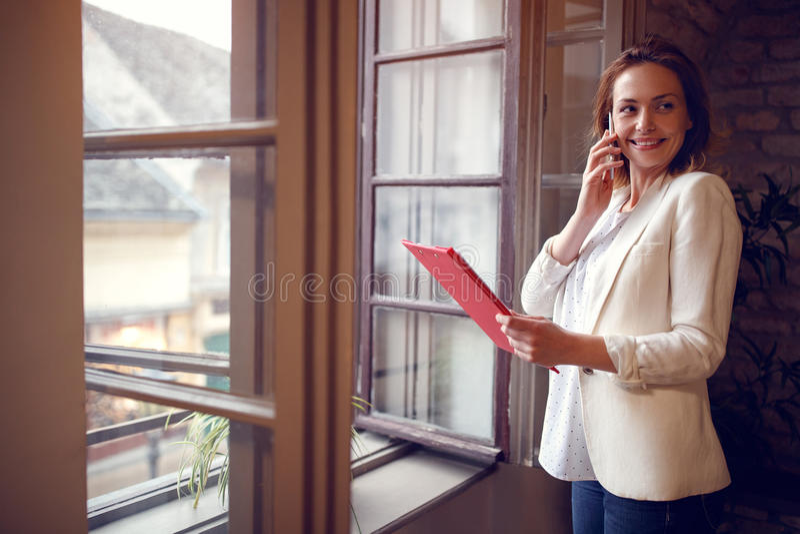 Encargado de sexo femenino joven en el teléfono celular en compañía imagen de archivo libre de regalías