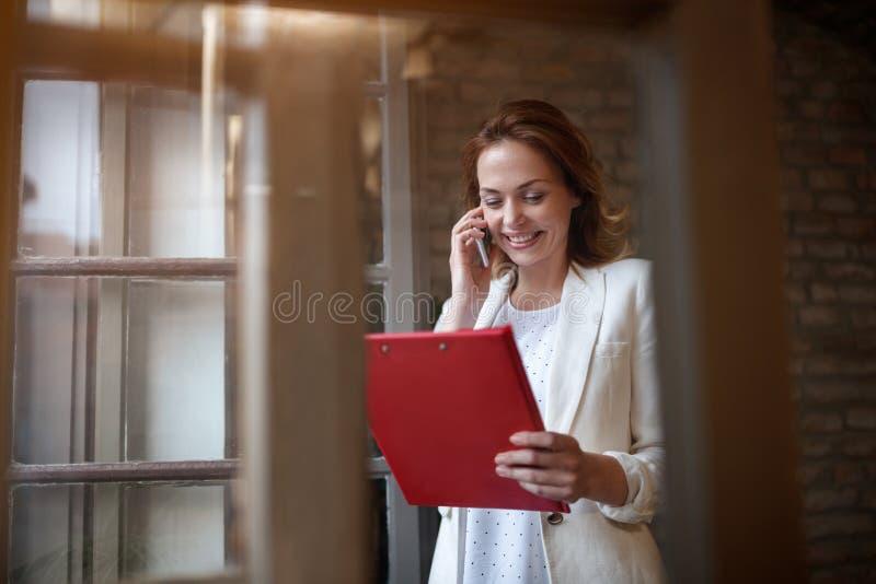 Encargado de sexo femenino que habla en el teléfono celular con el empleado fotografía de archivo