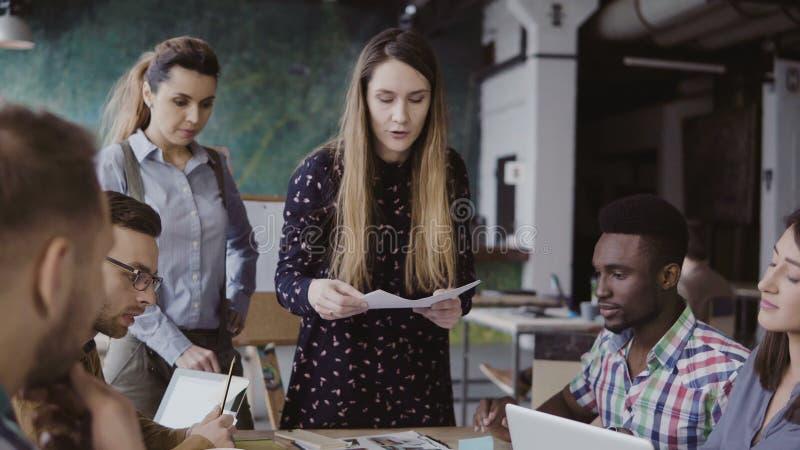 Encargado de sexo femenino que presenta el proyecto, distribuyendo el documento de papel Reunión de negocios del equipo joven de  fotos de archivo