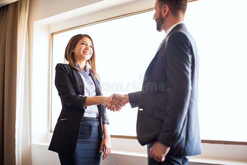 Encargado de sexo femenino que sacude las manos con un compañero de trabajo fotos de archivo