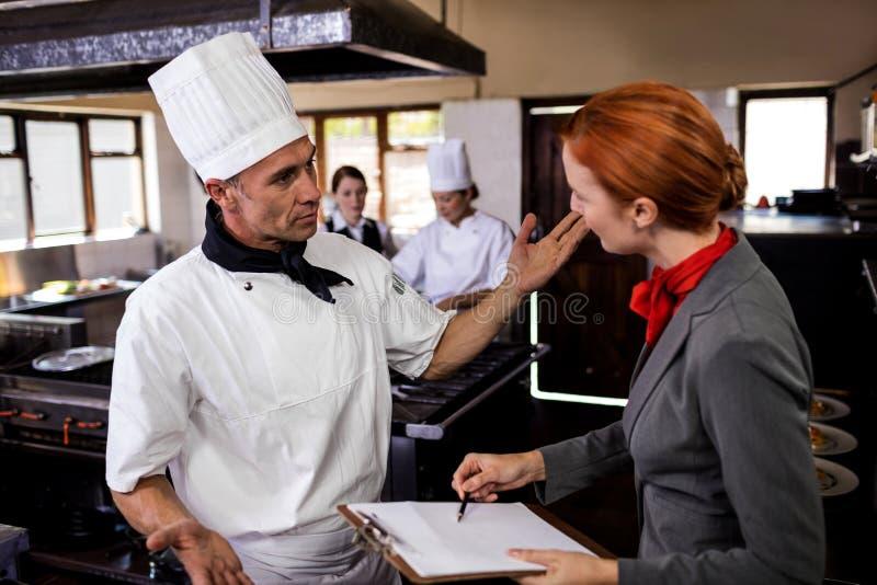 Encargado de sexo femenino y cocinero de sexo masculino que obran recíprocamente con uno a en cocina foto de archivo libre de regalías