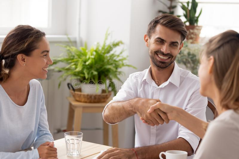 Encargado de sexo masculino cauc?sico sonriente, socio que sacude las manos agradeciendo al compa?ero de trabajo foto de archivo libre de regalías