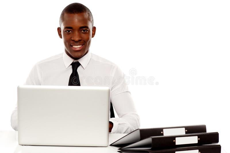 Encargado de sexo masculino corporativo africano en el escritorio del trabajo foto de archivo