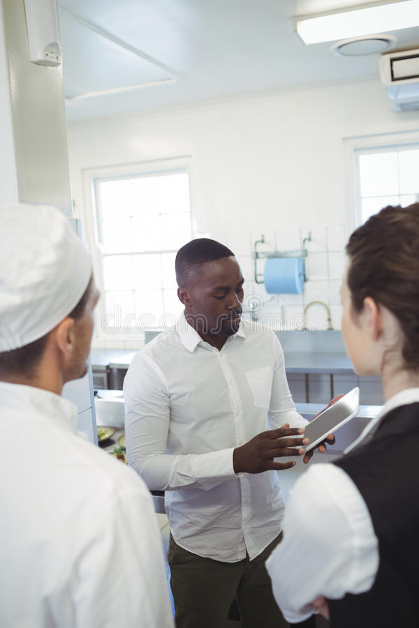 Encargado de sexo masculino del restaurante que usa la tableta digital mientras que informa a su personal de la cocina fotos de archivo