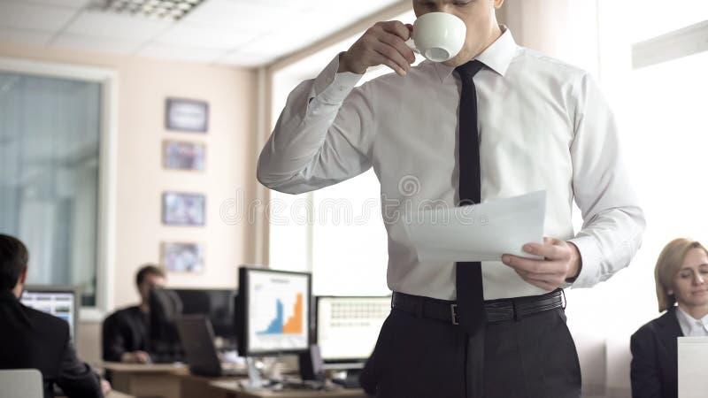 Encargado de sexo masculino que mira a trav?s de la documentaci?n y del caf? de consumici?n, trabajo de oficina foto de archivo